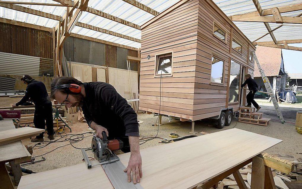 Een traditioneel tiny house staat op wielen en is zo klein dat je het met een trekhaak kunt verplaatsen. Foto: tiny house in aanbouw in een werkplaats in Frankrijk. beeld AFP Damien Meyer