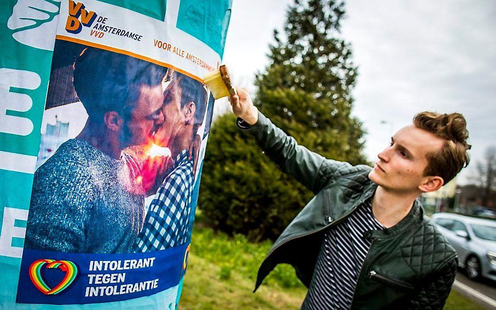"""""""Seksualiteit is een bijzonder geschenk van God bij de schepping, maar dat mag niet los gezien worden van die onverbrekelijke verbintenis tussen één man en één vrouw."""" Foto: postercampagne van de VVD in Amsterdam met zoenende mannen, begin maart. beeld AN"""