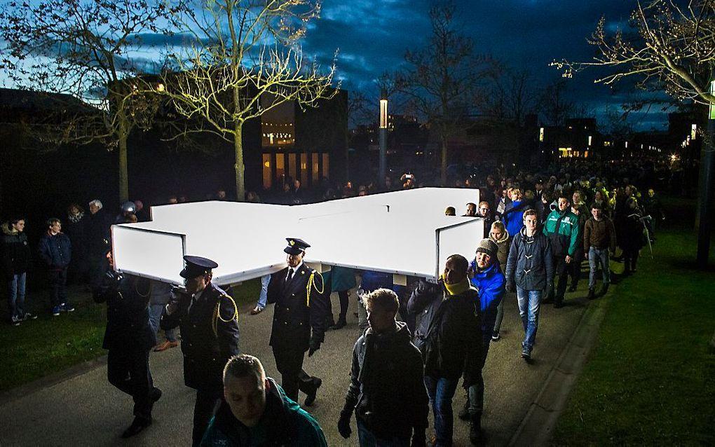 Mensen dragen voor het muziekspektakel The Passion op 2 april 2015 een groot verlicht kruis door de straten van de wijk Roombeek in Enschede.  beeld ANP