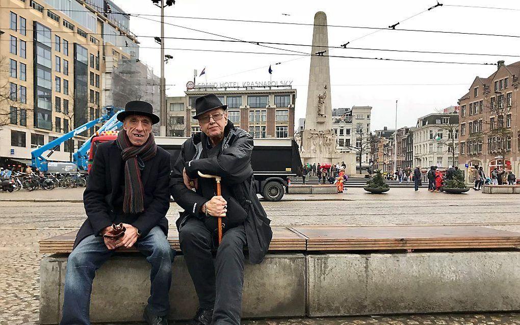 Twee Britten eten een broodje op een betonblok in Amsterdam. beeld Gerard ten Voorde