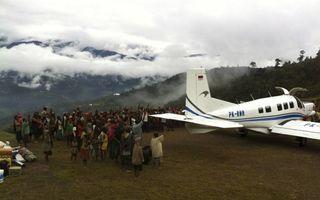 Vliegen op Papoea vraagt veel van de piloot. Het eiland wordt door kenners beschouwd als een van de gevaarlijkste regio's ter wereld om te vliegen. Foto: inwoners van het dorp Ipdeheik bidden voor een veilige vlucht, foto Geerten Vreugdenhil