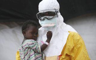 Een medewerker van Artsen zonder Grenzen in beschermende kleding houdt een kind vast dat vermoedelijk besmet is met ebola (Paynesville, Liberië). Beeld Getty Images
