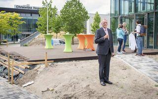 """Drs. M. Burggraaf voor het oude (l) en het nieuwe gebouw van de Christelijke Hogeschool Ede. """"Als ik in Rotterdam was gebleven, was ik mogelijk wat vastgeroest."""" beeld Niek Stam"""