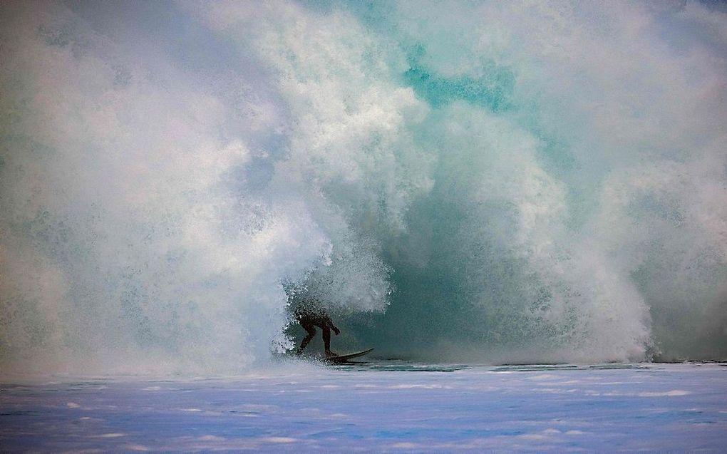 Een surfer op surflocatie Banzai Pipeline voor de kust van het Hawaïaanse eiland Oahu. beeld AFP, Brian Bielmann