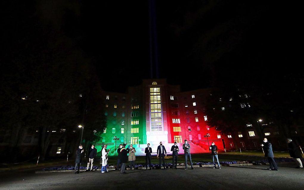 Het Spedali Civiliziekenhuis in de Italiaanse stad Brescia, verlicht in de nationale kleuren, ter nagedachtenis aan de vele coronaslachtoffers die inmiddels in het land te betreuren zijn. beeld EPA, Filippo Venezia