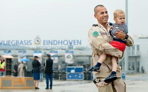 Een militair wordt op vliegveld Eindhoven verwelkomd door zijn kind. beeld ANP, Bart Maat