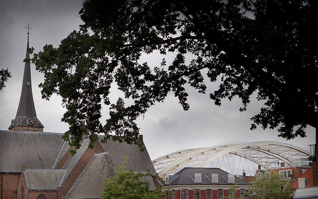 De Adriaen Janszkerk te Rotterdam-IJsselmonde, met op de achtergrond de Van Brienenoordbrug. beeld RD, Henk Visscher