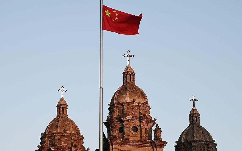 De Chinese nationale vlag voor de rooms-katholieke Sint-Jozefskerk in Peking. beeld AFP, Greg Baker
