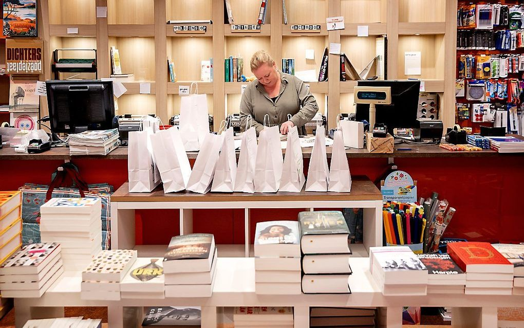 Een boekhandelaar in Alkmaar pakt bestellingen in. beeld ANP, Koen van Weel