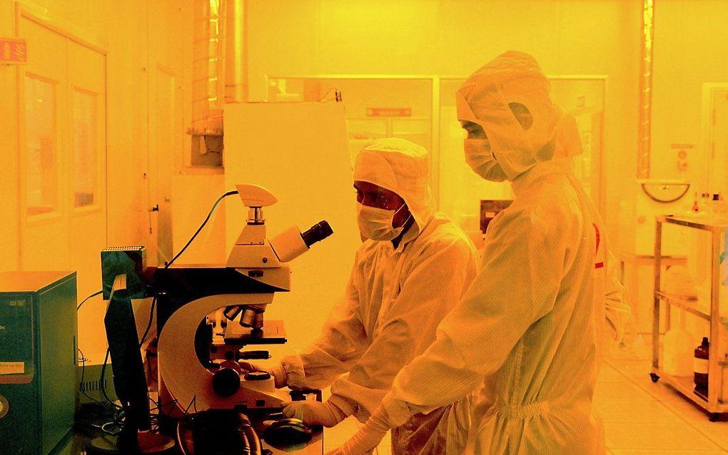 Onderzoekers in beschermende pakken aan het werk in het Centre for Nano Science and Engineering in Bangalore, India. beeld AFP, Manjunath Kiran