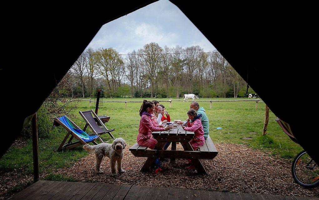Een gezin kampeert bij boerin Thea bij Boerenbed op Landgoed Volenbeek. Omdat vakantie in het buitenland voorlopig vanwege de coronamaatregelen de nodige voeten in de aarde heeft, is er veel vraag naar vakanties in eigen land. beeld ANP, Robin van Lonkhuijsen