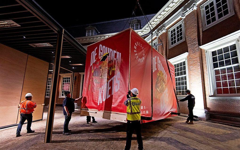 Met een enorme hijskraan is de Gouden Koets naar de binnenplaats van het Amsterdam Museum getakeld. De gerestaureerde Gouden Koets, die ruim 2.800 kilo weegt, is hier als middelpunt van een gelijknamige tentoonstelling acht maanden lang van dichtbij te zien voor publiek. beeld ANP, Olaf Kraak