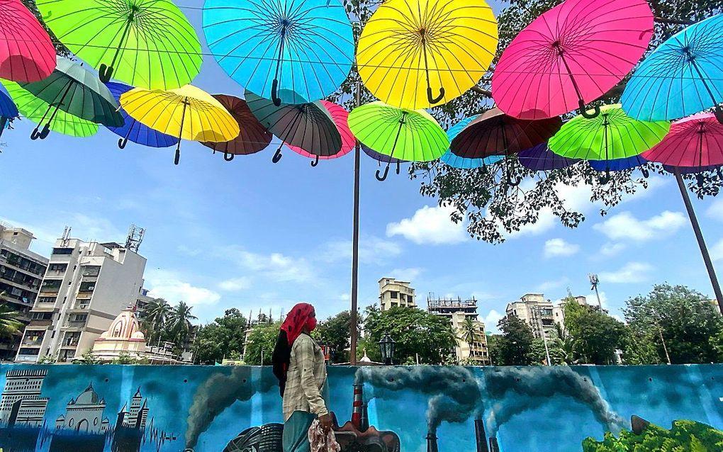 Een kunstwerk van gekleurde paraplu's in Mumbai, India. beeld AFP, Indranil MUKHERJEE