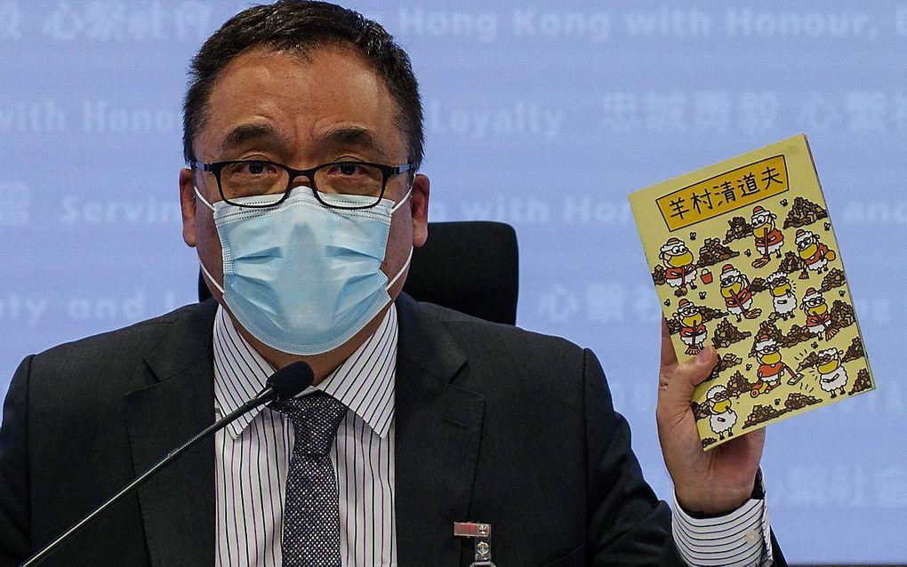 Politiefunctionaris Steve Li toont drie kinderboeken op een persconferentie. beeld AFP, Daniel Suen