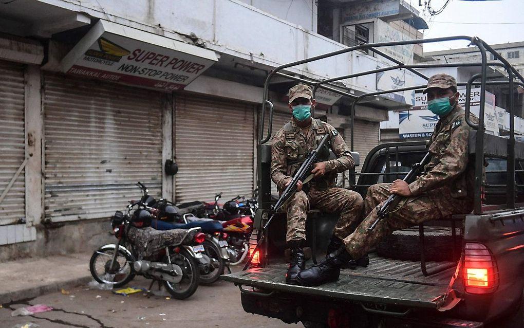 Pakistaanse militairen patrouilleren bij een gesloten markt. beeld AFP, Asif Hassan