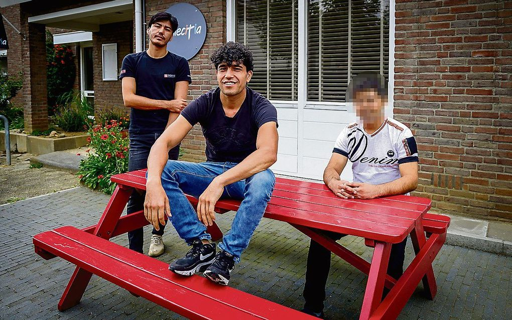De Afghanen Naser (l.),  Hussein (midden) en Yama (om veiligheidsredenen is zijn gezicht onherkenbaar gemaakt). beeld Jean-Pierre Geusens