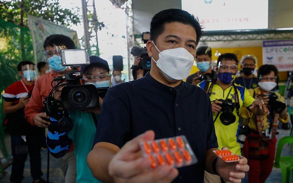 Een Filipijnse man met ivermectinecapsules. In Quezon City wordt het antiwormmiddel gratis verstrekt door artsen die menen dat het tegen Covid-19 werkt. beeld EPA, Rolex dela Pena