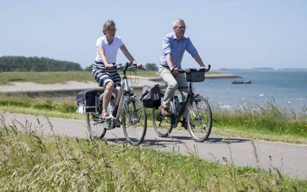 """Hendrik Boot (48) en Willy Boot-Sinke (49) fietsen graag langs het water. """"Als we terugkomen van vakantie, fietsen we op zaterdagmiddag vaak even naar de Oosterschelde. Als we die gezien hebben, zijn we echt weer terug in Zeeland."""" beeld Dirk-Jan Gjeltem"""