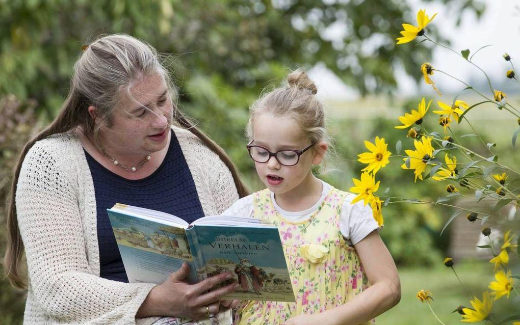 """Gisette van Dalen-Heemskerk leest haar jongste dochter voor uit """"Bijbelse verhalen voor kinderen"""". beeld RD, Anton Dommerholt"""