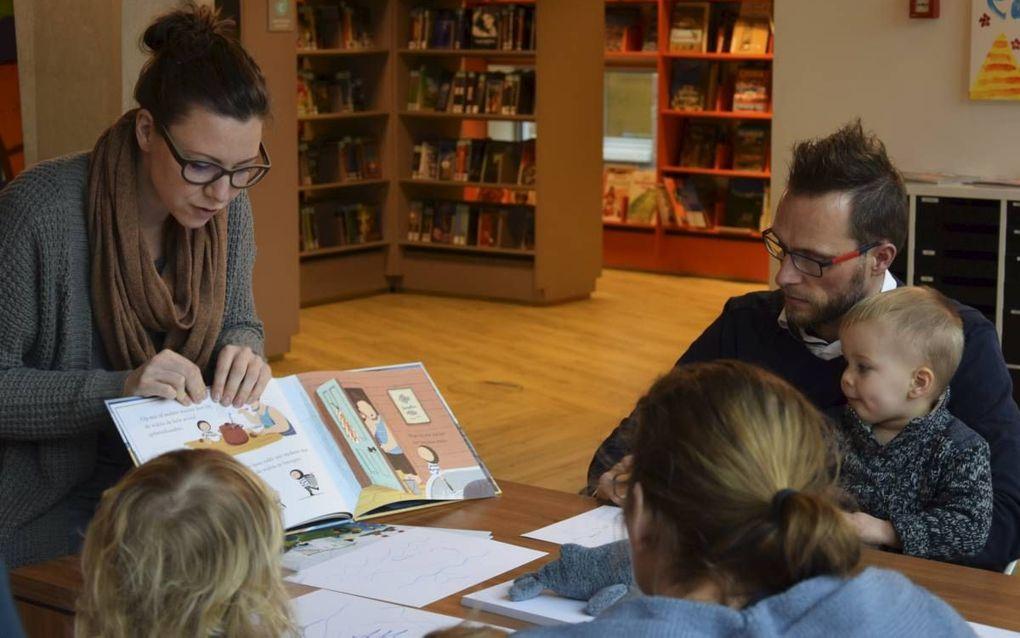 Kunstenaar Sabine Delhez wijst op plaatjes in het prentenboek waarover peuters en hun ouders een tekening maken tijdens het Mamacafé, een van de vele activiteiten in de bibliotheek van Veenendaal.