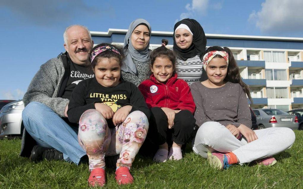 Vader Jarah met zijn gezin voor hun appartement even buiten het centrum van Reykjavik. Moeder Fotoun Nahlawi (37) en haar oudste dochters Wafika (17) dragen een hoofddoek. Dat geld nog niet voor de drie dochters Masa (13), Bailesam (7) en Ritaj (5). beeld