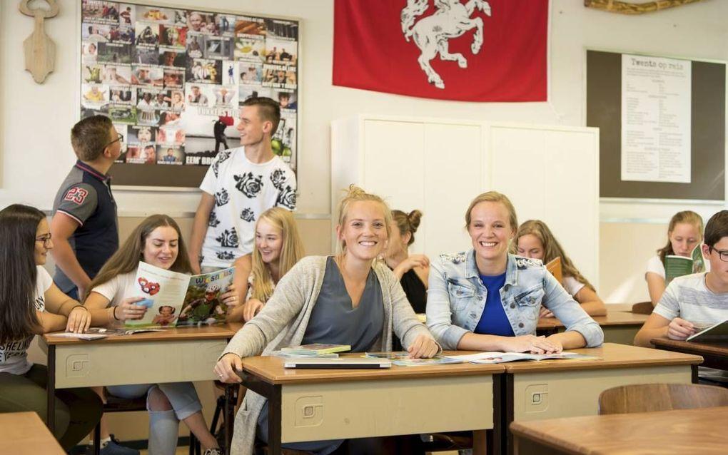 Docente Nederlands Marieke van den Brink (r) van het Noordik College in Almelo heeft haar lokaal ingericht met Twentse materialen. Foto: Van den Brink  samen  met Willemijn Zwart van de IJsselacademie en een aantal leerlingen. beeld Jan van de Maat