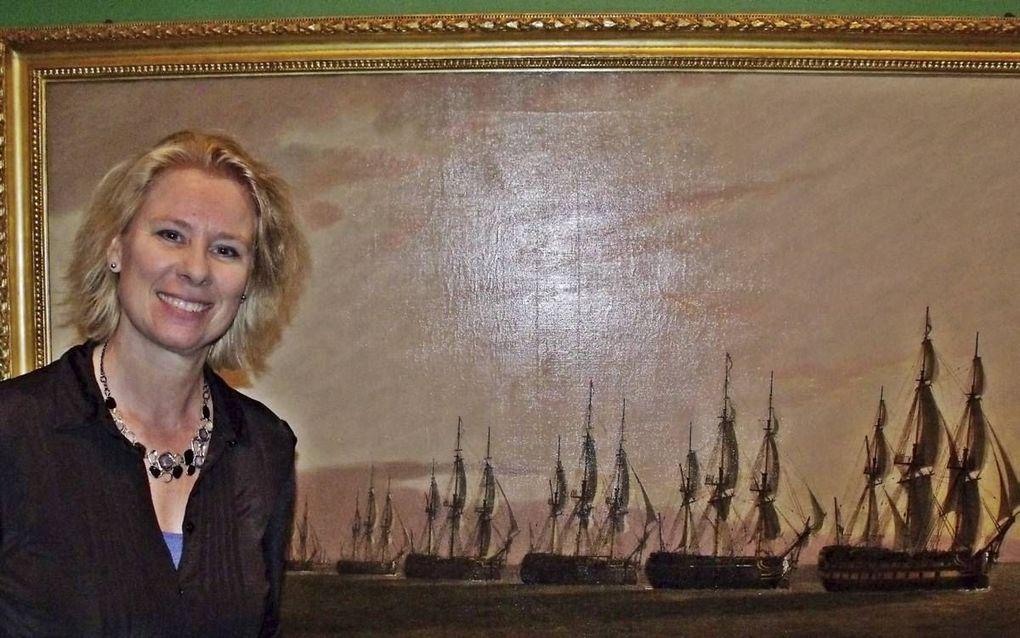 Conservator Irene Jacobs van het Maritiem Museum Rotterdam bij het schilderij van de Engelse schilder Thomas Luny, die de kaping bij Sint-Helena vastlegde.beeld Dick den Braber