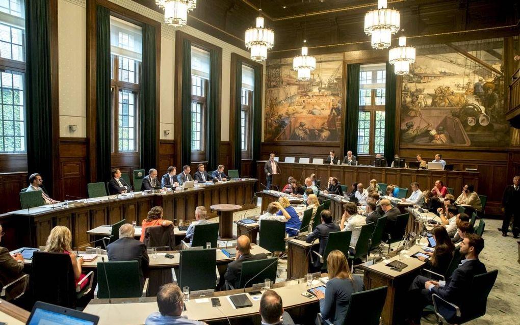 De raadszaal in Rotterdam, met links het college van Burgemeester en Wethouders en midden en rechts een aantal raadsleden. beeld ANP, Jerry Lampen