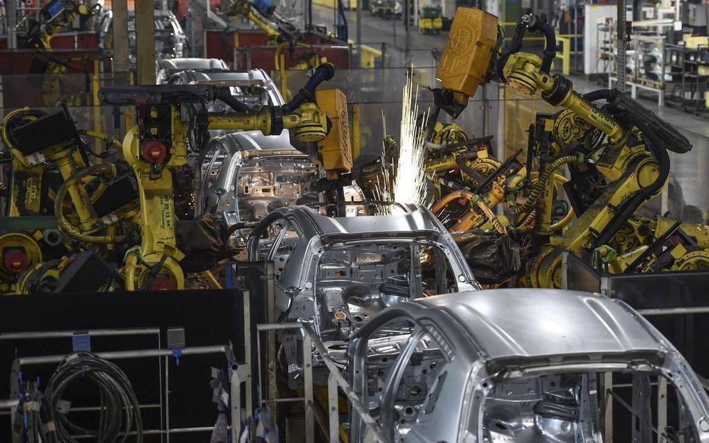 """""""Globalisering en automatisering zijn de arbeidsmarkt op een ontwrichtende manier aan het veranderen. Een blik in een moderne autofabriek zegt genoeg; overal robots."""" Foto: Robots in de fabriek van PSA Peugeot Citroen in het Franse Mulhouse. beeld AFP, Sé"""