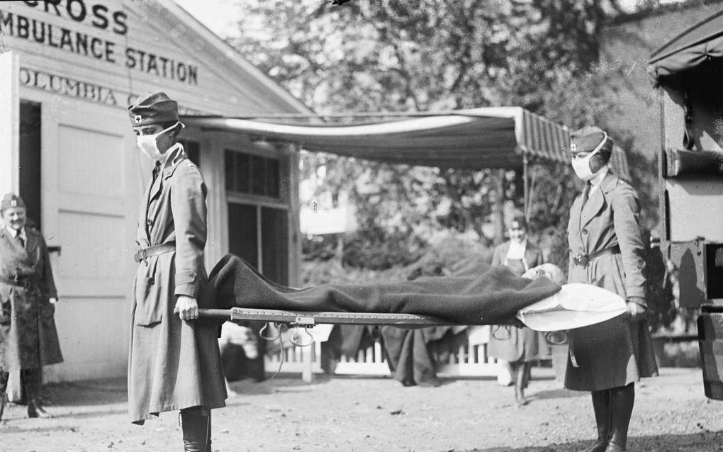 Twee Amerikaanse verpleegsters dragen een grieppatiënt weg. De epidemie velde veel soldaten en beïnvloedde het eind van de Eerste Wereldoorlog.beeld National Photo Company / LCC