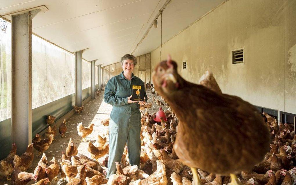 """Gerda Briene temidden van haar biologische kippen. De boerin uit Wierden presenteerde het eerste exemplaar van haar boek over de fipronilcrisis aan burgemeester Van Dijk van Barneveld, """"een man met het hart op de juiste plaats.""""beeld Jan van de Maat"""