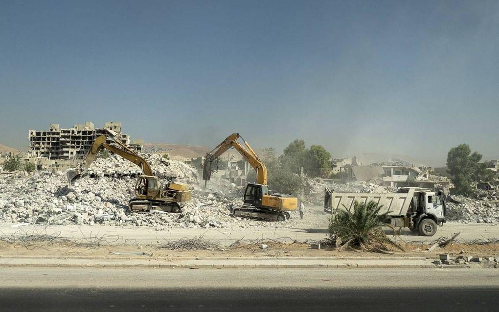 Graafmachines aan het werk tussen de vernietigde gebouwen in de Syrische stad Douma. De komende tijd zal duidelijk worden wie er gaat meebetalen aan de wederopbouw van Syrië en onder welke voorwaarden.beeld AFP, Andrey Borodulin