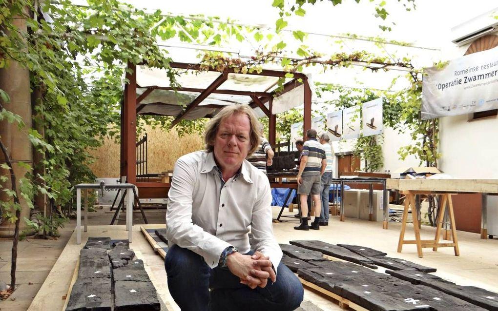 Archeoloog Tom Hazenberg (1963). Achter hem een deel van zijn restauratieteam.
