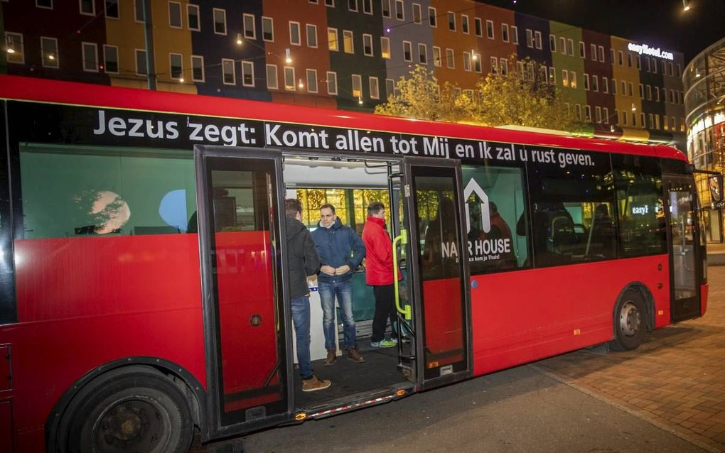De evangelisatiebus van stichting Naar House, geparkeerd voor de deur van concertzaal AFAS live.beeld Martin Mooij
