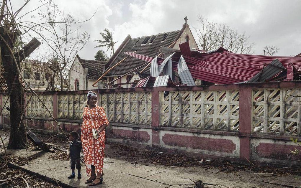 Een vrouw met haar kind staat bij beschadigde gebouwen in Beira, Mozambique, afgelopen zondag. Het grootste deel van Beira ligt in puin, nadat een verwoestende orkaan door de stad raasde. beeld Internation Federation of Red Cross and Red Crescent Societie