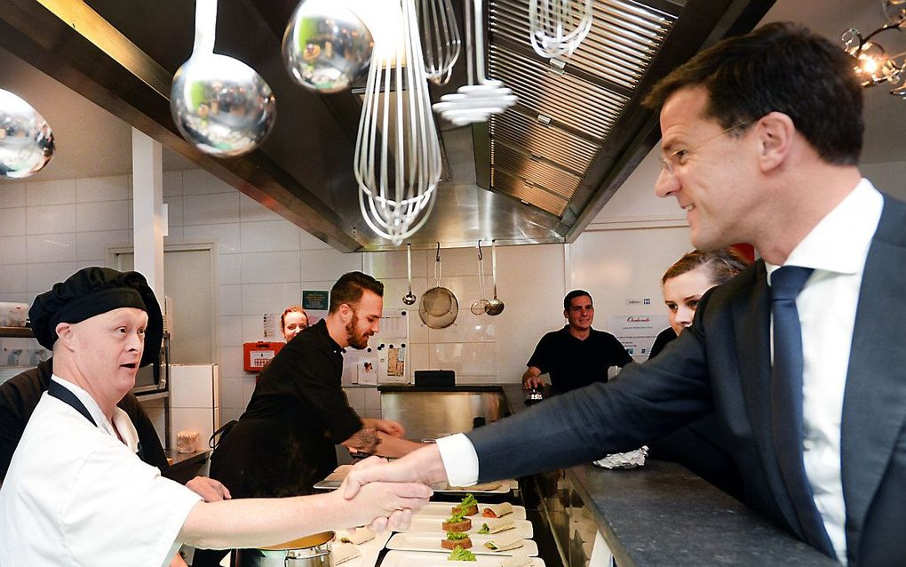 Premier Mark Rutte groet een werknemer van een restaurant in Almelo dat wordt gerund door mensen met een licht verstandelijke beperking. beeld ANP, Piroschka van de Wouw
