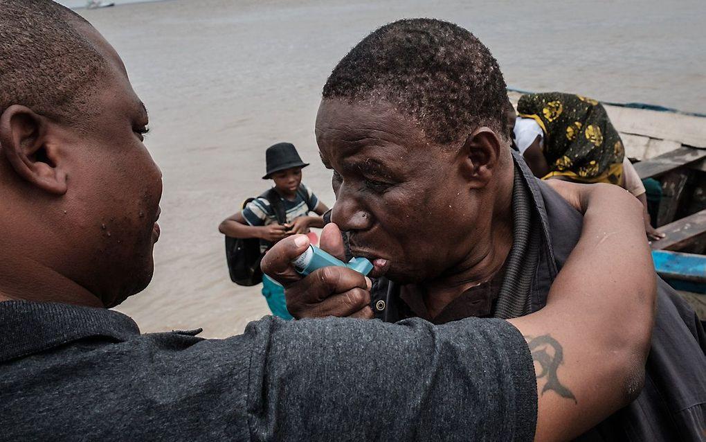 Een Mozambicaan neemt een astmapuffer. Patiënten met astma die goed onder controle is, lopen niet meer risico op een ernstig verloop van Covid-19. beeld AFP, Yasuyoshi Chiba