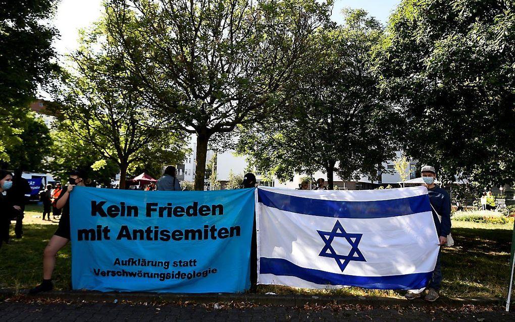 Duitse kerken ondernemen gezamenlijk actie tegen antisemitisme in een postercampagne. Archiefbeeld: Demonstranten tonen vlaggen tegen Jodenhaat bij de start van het proces tegen de man die een aanslag pleegde op een synagoge in het Duitse Halle. beeld AFP