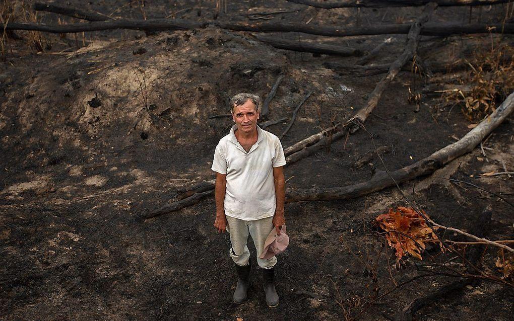 Een Braziliaanse boer tussen de resten van zijn boerderij in de Amazone. beeld EPA
