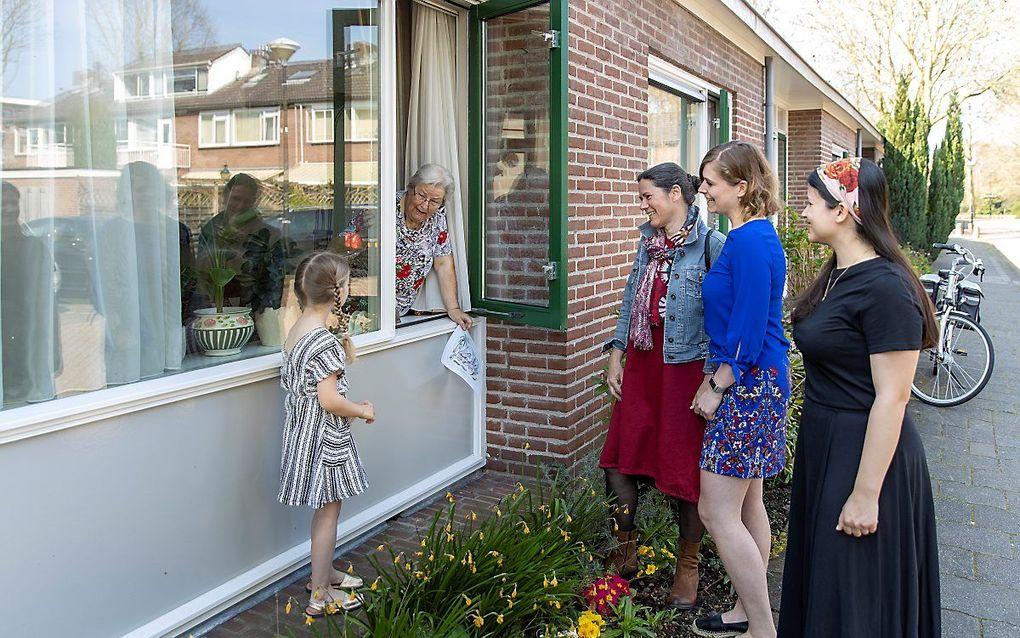 De 86-jarige Cornelia Smit-Ligtenberg uit Vinkeveen krijgt raambezoek van haar 5-jarige achterkleindochter Avia (5), schoondochter Christine (50) en kleindochters Kyra (23) en Sara-Maria (24, rechts op de foto)beeld RD, Henk Visscher