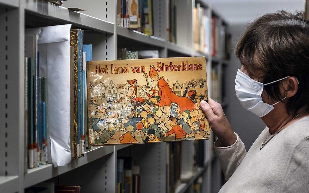 Een medewerker van de Openbare Bibliotheek Amsterdam (OBA) toont een boek met Sinterklaas en Zwarte Piet. De bibliotheek verplaatst de kinderboeken met een traditionele Zwarte Piet van het museum naar de kluis. beeld ANP RAMON VAN FLYMEN