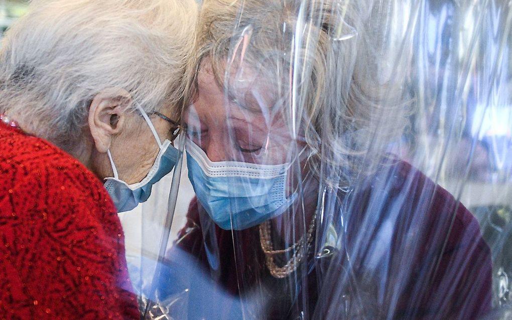 """Een bewoner van verpleeghuis Domenico Sartor in Castelfranco Veneto, nabij Venetië, knuffelt haar bezoekende dochter op 11 november 2020 door een plastic scherm in een zogenaamde """"Hug Room"""" te midden van de nieuwe coronavirus-pandemie. In de Hug Room kunn"""