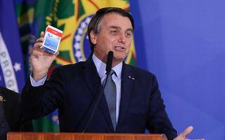 De Braziliaanse president Bolsonaro met een pakje hydroxychloroquine, september dit jaar. beeld AFP, Sergio Lima