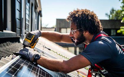 Een installateur plaatst zonnepanelen op het dak van een woonhuis. beeld ANP, Remko de Waal