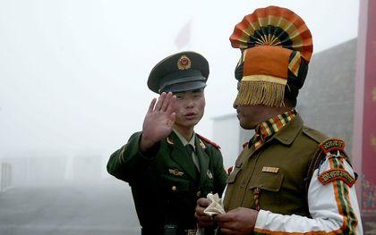 Een Chinese en Indiase grenssoldaat groeten elkaar. beeld Diptendu DUTTA / AFP