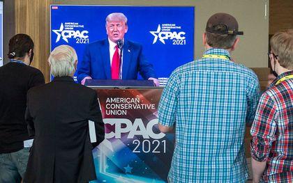 Mensen kijken naar de toespraak van Trump tijdens CPAC. beeld  EPA, CRISTOBAL HERRERA-ULASHKEVICH