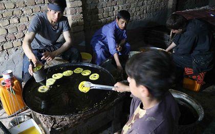 Jongens bereiden een maaltijd in de Afghaanse stad Herat. beeld EPA, Jalil Rezayee