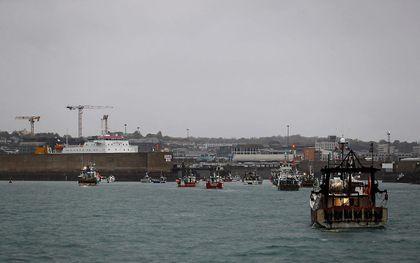 Franse vissersboten protesteren voor de haven van Saint Helier bij het Britse eiland Jersey om de aandacht te vestigen op wat zij beschouwen als oneerlijke beperkingen op hun vermogen om in de Britse wateren te vissen. beeld AFP, Sameer Al Doumy