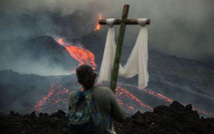 Een persoon met een kruis kijkt naar de lava die langs de Pacaya-vulkaan stroomt, in San Vicente Pacaya, Guatemala. Katholieke inwoners van het dorp El Patrocinio hebben de afgelopen zeven weken elke woensdag een pelgrimstocht gemaakt om te bidden dat de lava de nabijgelegen steden niet zou bereiken. beeld EPA, Esteban Biba