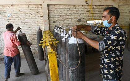 Een man in India hervult zuurstofflessen. Het aantal positieve tests in India is torenhoog, de ziekenhuizen liggen overvol. Christelijke hulporganisaties starten een inzamelingsactie voor het getroffen land. beeld AFP, Prakash Singh
